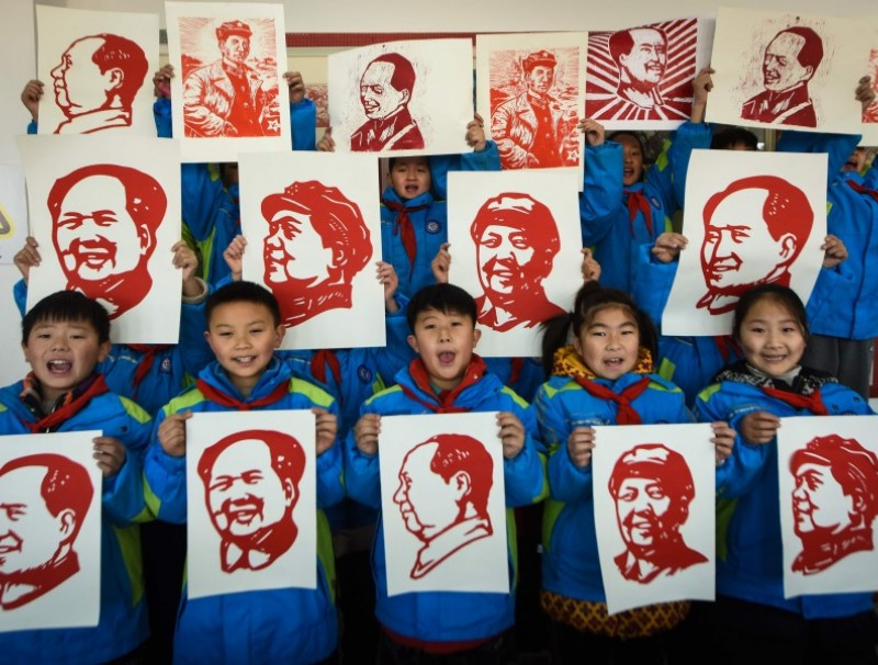 Students display their paper cutting portraits of the late former Chinese Communist Party leader Mao Zedong ahead of his 127th birthday which falls on 26 December, in Lianyungang in eastern China's Jiangsu province on 23 December 2020. (STR/AFP)