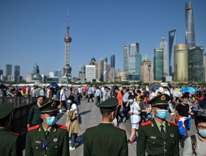 People visit the promenade on the Bund along the Huangpu River, 1 May 2021, Shanghai, China. (Hector Retamal/AFP)