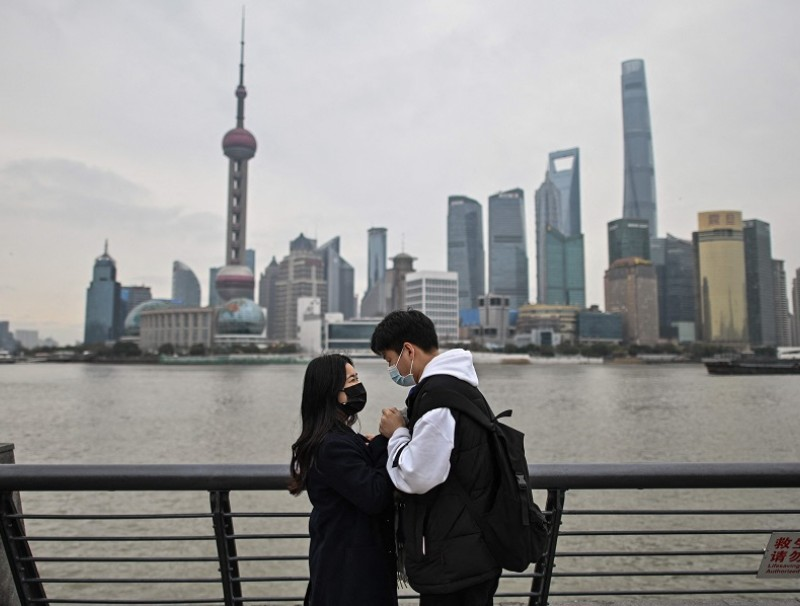 In this photo taken on 5 March 2021, a couple visits the promenade on the Bund along Huangpu River in Shanghai, China. (Hector Retamal/AFP)