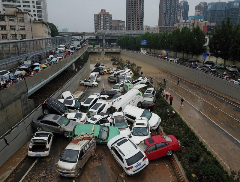 An aerial view shows cars sitting in floodwaters at the entrance of a tunnel after heavy rains hit the city of Zhengzhou in China's central Henan province on 22 July 2021. (Noel Celis/AFP)
