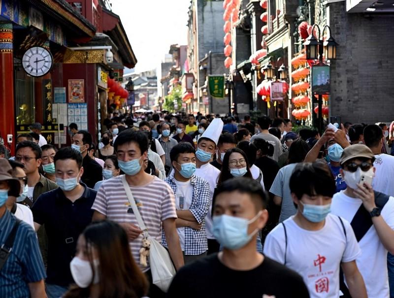 People walk in Qianmen street in Beijing, China, on 21 September 2021. (Noel Celis/AFP)
