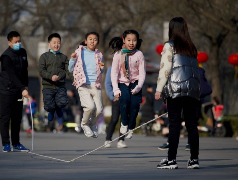 Children play a jump rope game in a park in Beijing on 9 February 2021. (Noel Celis/AFP)