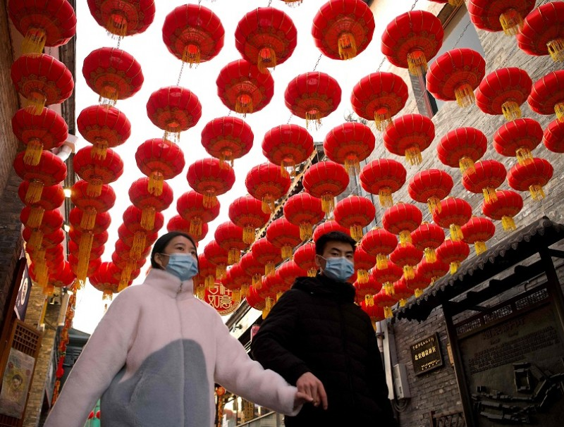 People walk under traditional Chinese lanterns along an alley in Beijing on 9 February 2021, ahead the biggest holiday of the year, the Lunar New Year, which ushers in the Year of the Ox on 12 February. (Noel Celis/AFP)