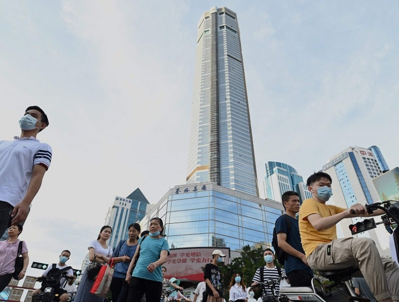 This file photo taken on 24 May 2021 shows people walking past the temporarily closed of 300 metre SEG Plaza (centre) in Shenzhen, Guangdong province, China. (Noel Celis/AFP)