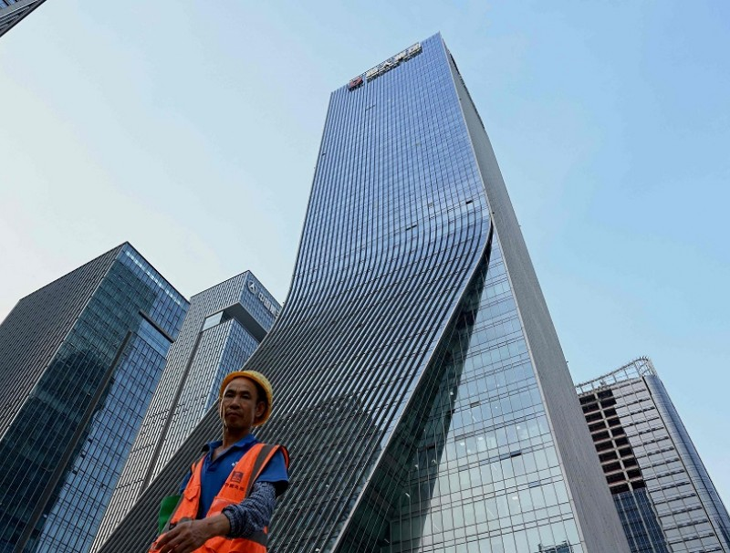 This file photo taken on 15 September 2021 shows a worker walking in front of the Evergrande headquarters in Shenzhen, Guangdong province, China. (Noel Celis/AFP)
