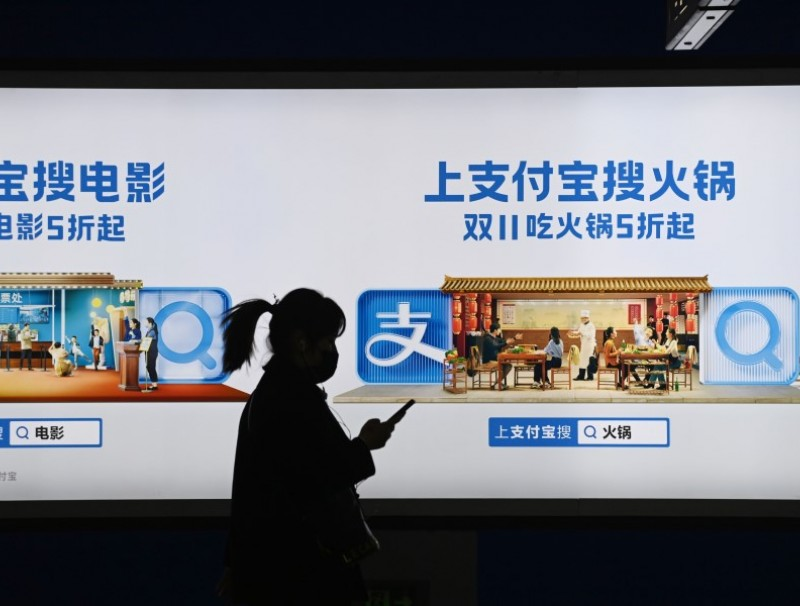 This file photo taken on 27 October 2020 shows a woman walking past an Alipay advertising billboard in a subway in Beijing. (Greg Baker/AFP)