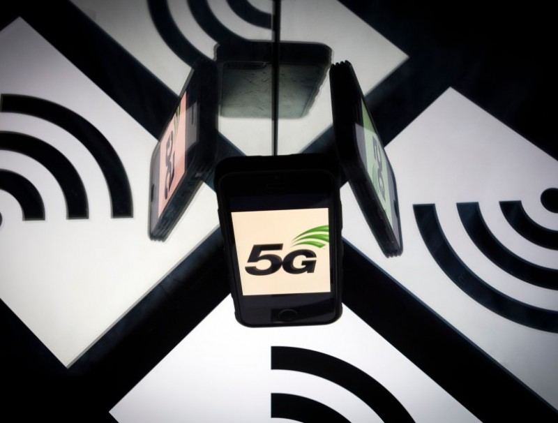 This illustration picture taken on 17 February 2019 shows the 5G wireless technology logo displayed on a smartphone and a wireless signal sign. (Lionel Bonaventure/AFP)