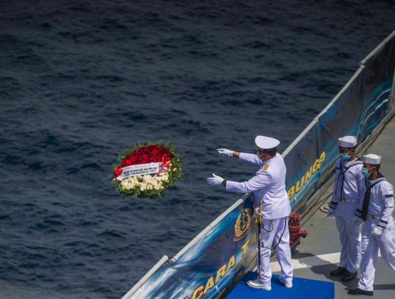 In this file photo taken on 30 April 2021, a naval officer throws a flower bouquet into the sea during a remembrance ceremony for the crew of the Indonesian navy submarine KRI Nanggala that sank on 21 April during a training exercise, on the deck of the hospital ship KRI Dr. Soeharso off the coast of Bali. (Juni Kriswanto/AFP)