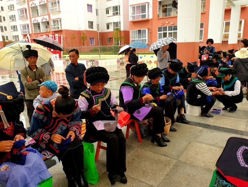 Yi women dressed in their traditional costumes are seen busying their hands with embroidery at the communal square of the Chengbei Thanksgiving Community. The government-built flats they have relocated to are seen in the background.