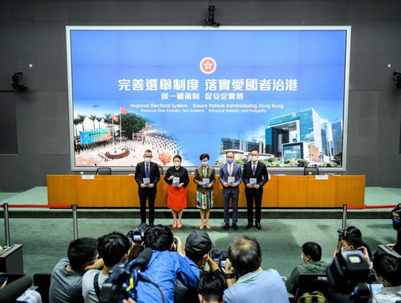Members of the media (bottom) take photos as (left to right) Acting Law Officer (Special Duties) Llewellyn Mui, Secretary for Justice Teresa Cheng, Hong Kong's Chief Executive Carrie Lam, Secretary for Constitutional and Mainland Affairs Erick Tsang and Permanent Secretary for Constitutional and Mainland Affairs Roy Tang arrive for a press conference at the government headquarters in Hong Kong on 13 April 2021. (Anthony Wallace/AFP)