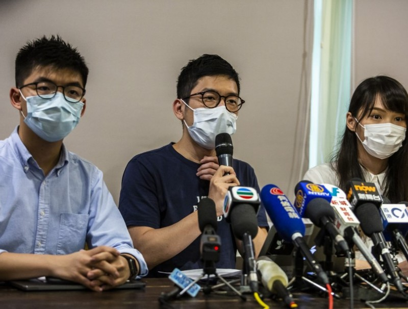 Joshua Wong (L), Nathan Law (C) and Agnes Chow (R) of pro-democracy political group Demosisto hold a press conference in Hong Kong on 30 May 2020. On 30 June, the three announced they were stepping down. (Isaac Lawrence/AFP)