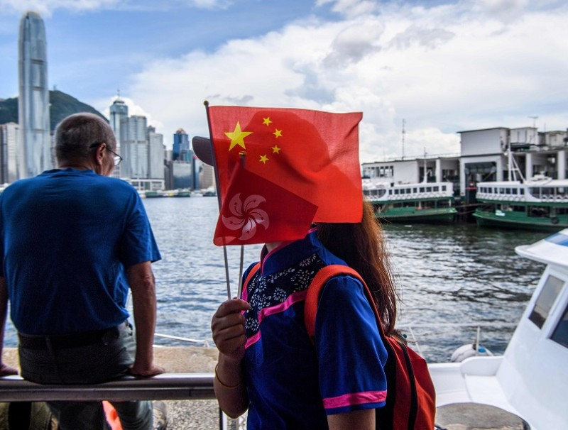 A member of a local community group holds Chinese and Hong Kong flags as she disembarks from a boat in Victoria Harbour on the 23rd anniversary of the city's handover from Britain in Hong Kong on 1 July 2020. (Anthony Wallace/AFP)