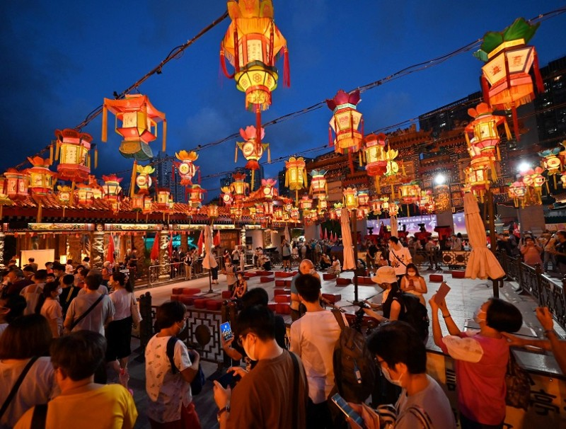 Visitors walk through a display of lanterns ahead of the mid-autumn festival at Wong Tai Sin temple in Hong Kong on 18 September 2021. (Peter Parks/AFP)
