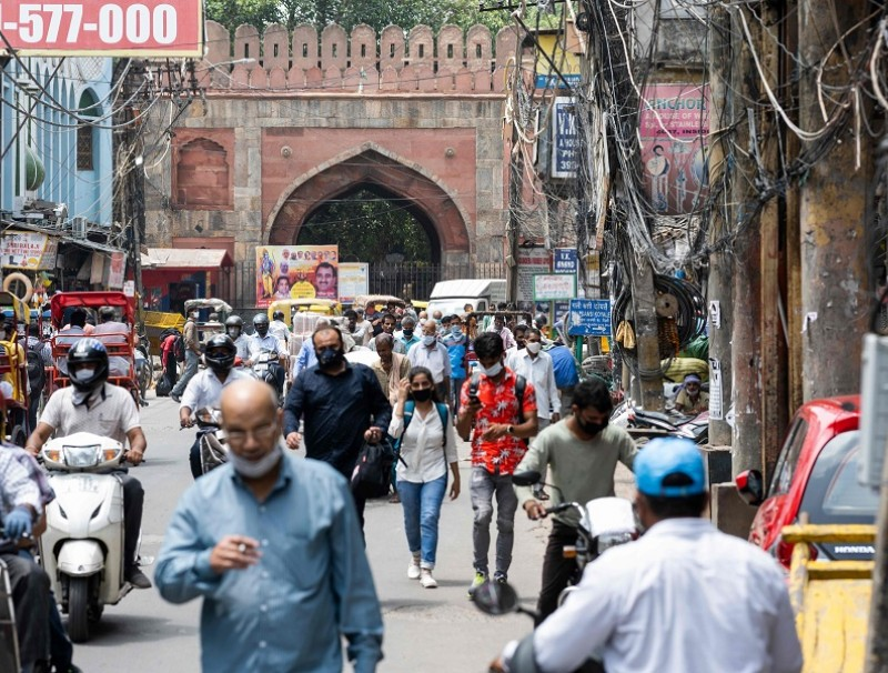 People make their way along a street in the old quarters of New Delhi on 7 August 2020. (Jewel Samad/AFP)