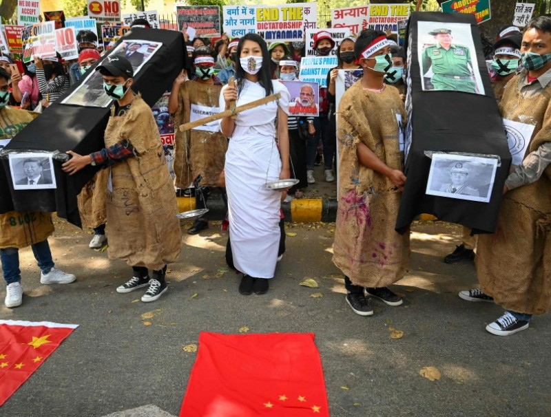 Protesters hold coffins displaying a picture of Chinese President Xi Jinping (left) and Myanmar military chief Senior General Min Aung Hlaing (right) during a demonstration in New Delhi on 3 March 2021, to protest against the military coup in Myanmar. (Prakash Singh/AFP)