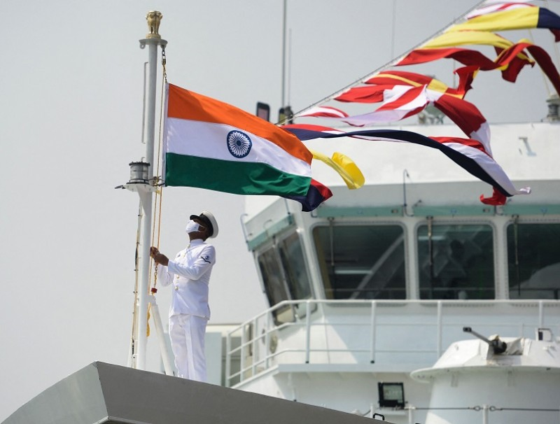 "A coast guard official raises the Indian national flag on board the Indian Coast Guard offshore patrol vessel ""Vajra"" during its commissioning ceremony, in Chennai, India, on 24 March 2021. (Arun Sankar/AFP)"