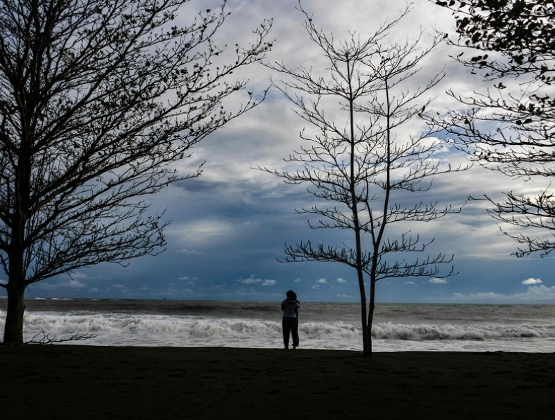 A woman looks out to the Indian Ocean at Meulaboh beach in Aceh on 12 July 2020. (Chaideer Mahyuddin/AFP)