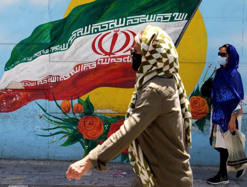 People wearing face masks walk past a mural displaying Iran's national flag in Tehran, Iran on 17 June 2021. (Atta Kenare/AFP)