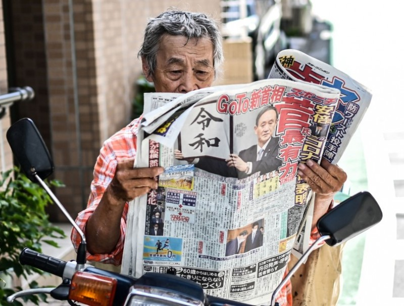A man reads a newspaper on a street in Tokyo, 29 August 2020. (Charly Triballeau/AFP)