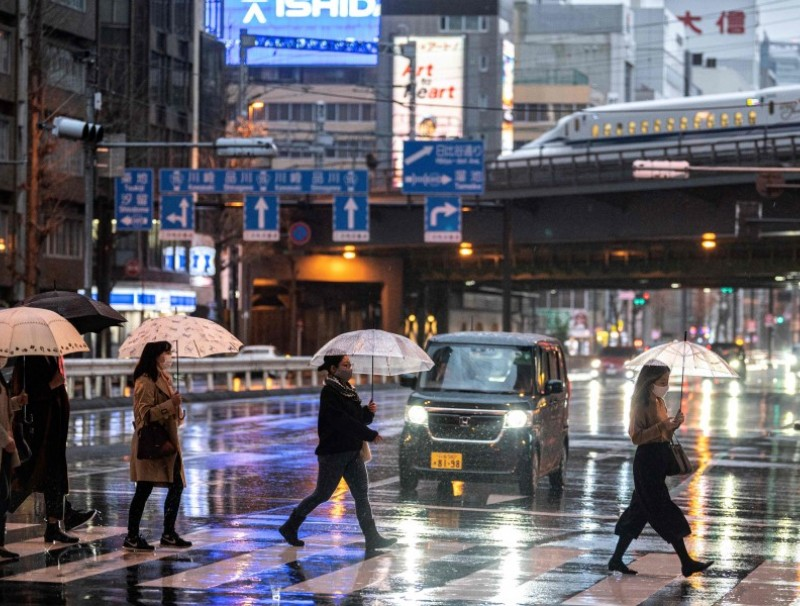 People cross a street under the rain at dusk while a shinkansen N700A series, or high speed bullet train, leaves Tokyo on 21 March 2021. (Charly Triballeau/AFP)