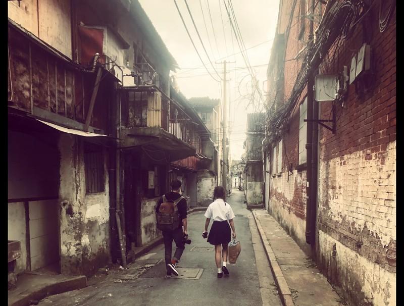 Boy and schoolgirl walk through a boarded-up neighbourhood in Laoximen.