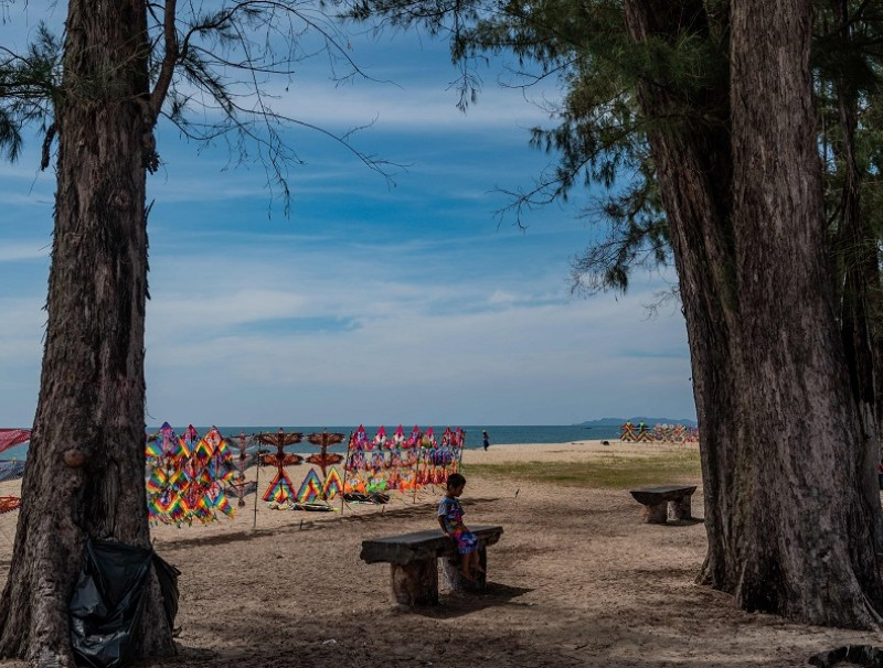 A boy sits on a bench on Batu Burok beach in Kuala Terengganu, in Malaysia by the South China Sea, on 26 June 2020. (Mohd Rasfan/AFP)