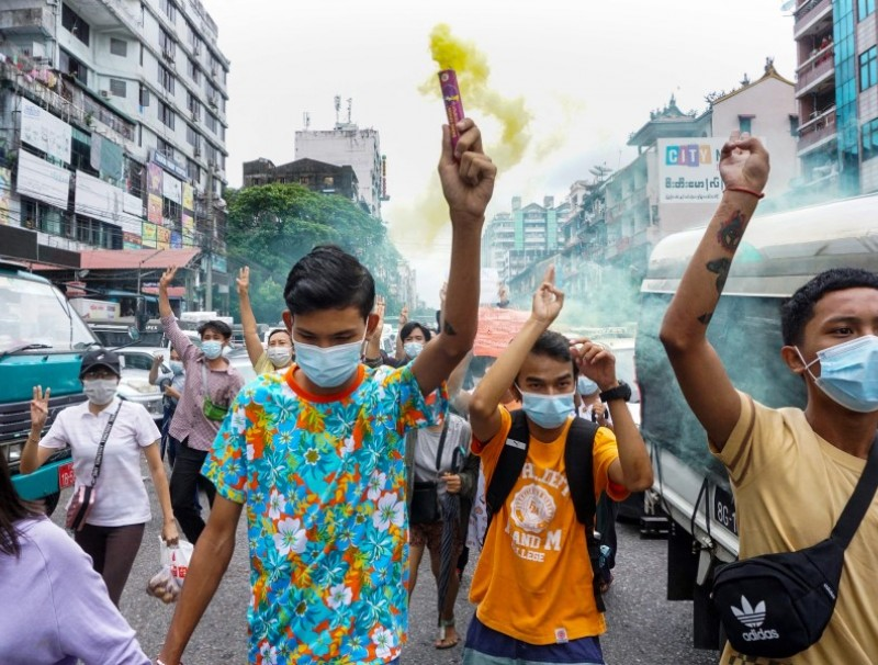 A protester holds a flare as others make the three-finger salute during a demonstration against the military coup in Yangon on 22 June 2021. (STR/AFP)