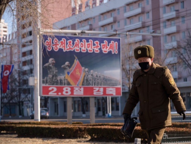 In a photo taken on 8 February 2021, a Korean People's Army (KPA) soldier walks past a poster displayed on a street in Pyongyang marking the 73rd anniversary of the foundation of the Korean People's Army. (Kim Won Jin/AFP)