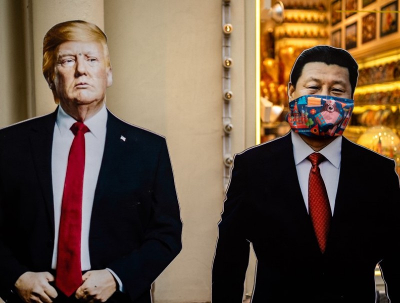 Cardboard figures of Chinese President Xi Jinping (R) wearing a face mask and US President Donald Trump (L) stand in front of a souvenir shop in downtown Moscow, 3 June 2020. (Dimitar Dilkoff/AFP