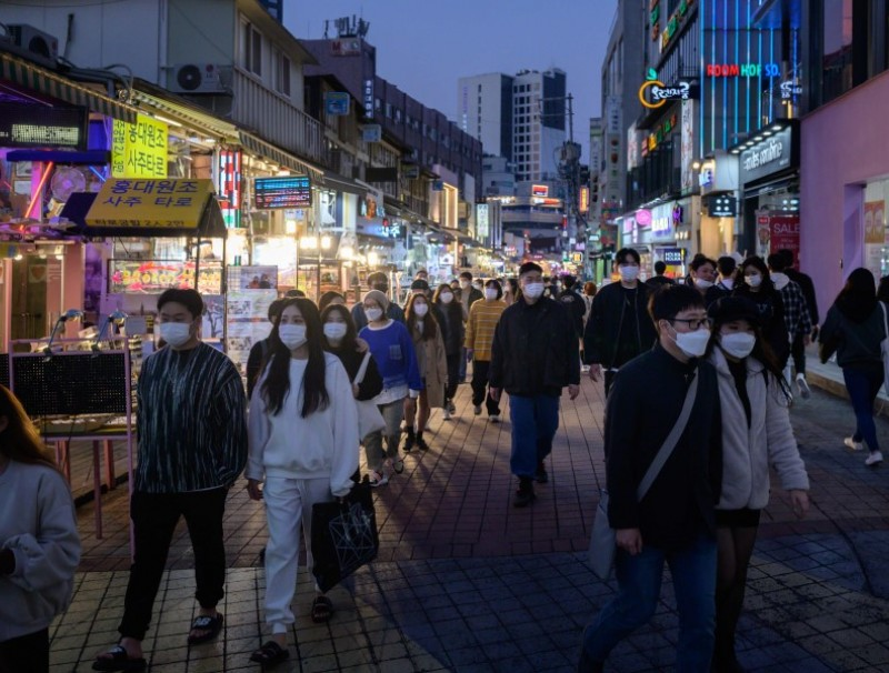 In a photo taken on 18 October 2020 people wearing face masks walk on a street in the Hongdae district of Seoul. (Ed Jones/AFP)