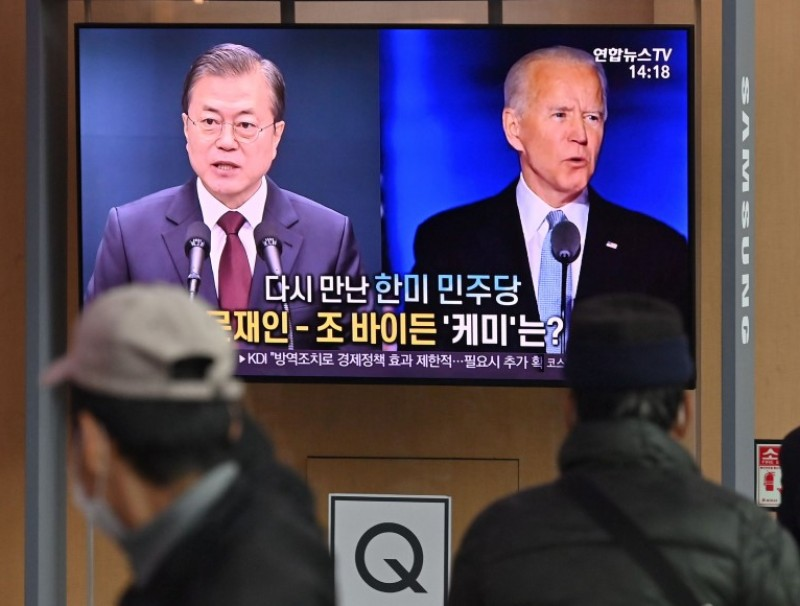 People watch a television news programme reporting on the US presidential election showing images of US President-elect Joe Biden (right) and South Korean President Moon Jae-in, at a railway station in Seoul on 9 November 2020. (Jung Yeon-je/AFP)