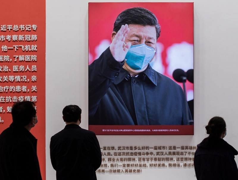 In this picture taken on 15 January 2021, a picture of Chinese President Xi Jinping with a face mask is displayed as people visit an exhibition about China's fight against the Covid-19 coronavirus at a convention centre that was previously used as a makeshift hospital for patients in Wuhan. (Nicolas Asfouri/AFP)