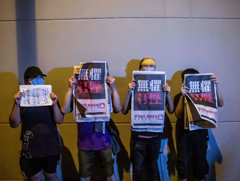 Supporters hold copies of the Apple Daily newspaper as Hong Kong pro-democracy media mogul Jimmy Lai is released on bail from the Mong Kok police station in Hong Kong on 12 August 2020, after his arrest under the new national security law. (Isaac Lawrence/AFP)