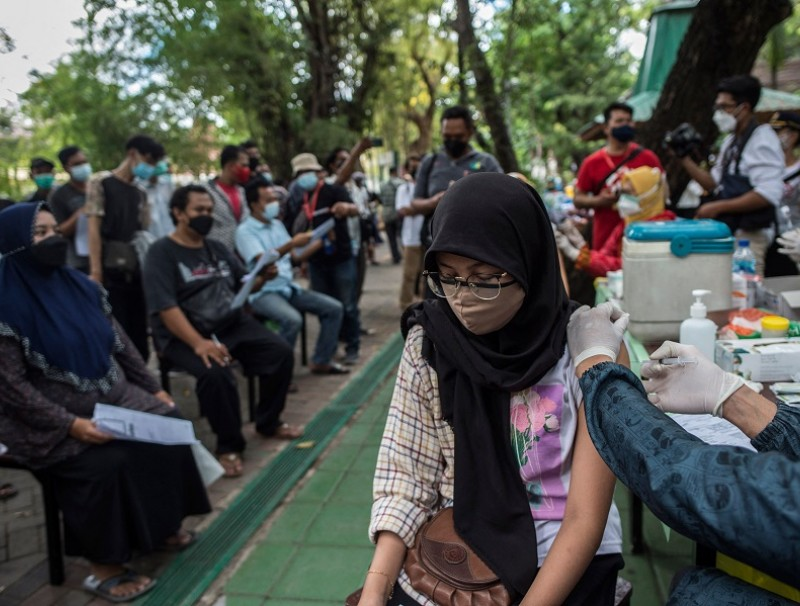 A health worker inoculates a woman with a dose of the Sinovac Covid-19 vaccine during a mass vaccination at a zoo in Surabaya, Indonesia, on 13 September 2021. (Juni Kriswanto/AFP)