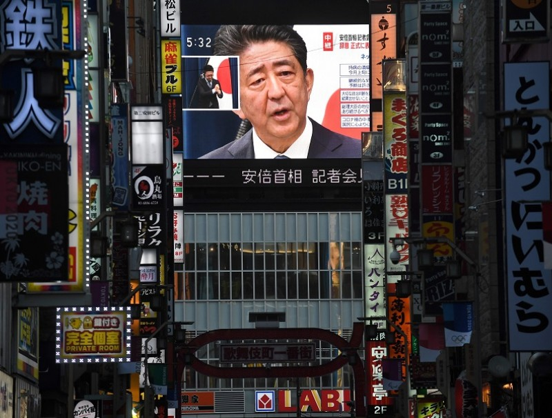 Japan Prime Minister Shinzo Abe is seen on a large screen during a live press conference in Tokyo on 28 August 2020. (Philip Fong/AFP)