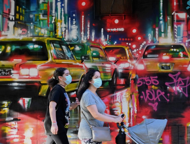 People walk past a mural on 26 May 2020 in New York City. (Angela Weiss/AFP)
