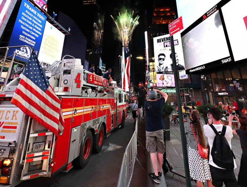 People watch as fireworks are launched in Times Square as part of the annual Macy's 4th of July Fireworks on 1 July 2020 in New York City. (Cindy Ord/Getty Images/AFP)