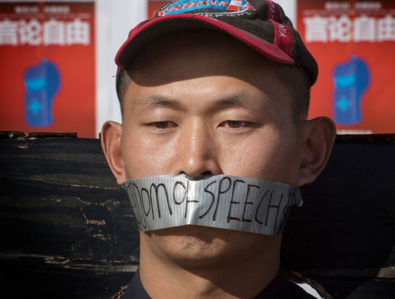 """Chinese students hold a memorial for Dr Li Wenliang outside the UCLA campus in Westwood, California, on 15 February 2020. In the photo, the student has the words """"freedom of speech"""" written on the duct tape over his mouth. (Mark Ralston/AFP)"""