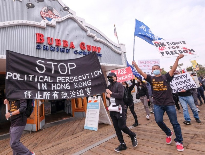Local natives of Hong Kong participate in a flash mob march to show solidarity with the 47 pro-democracy activists in Hong Kong who were charged for state subversion due to them organizing and taking part in a primary election, in Santa Monica, California on 7 March 2021. (Ringo Chiu/AFP)
