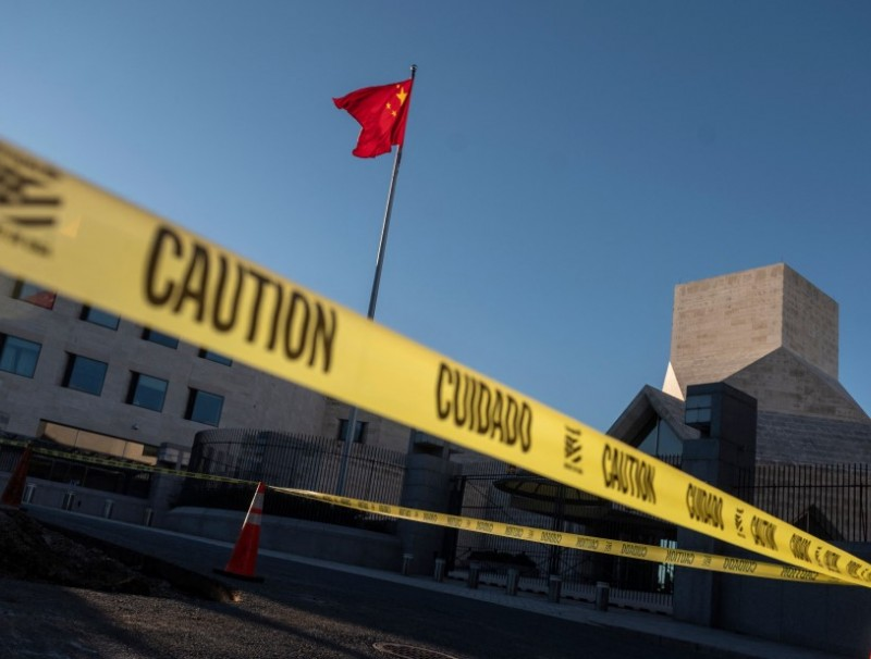 """Caution tape is seen near the Chinese embassy as activists hold a demonstration calling on Chinese President Xi Jinping to """"allow safe passage to North Koreans detained in China"""" in Washington, DC on 24 September 2021. (Andrew Caballero-Reynolds/AFP)"""