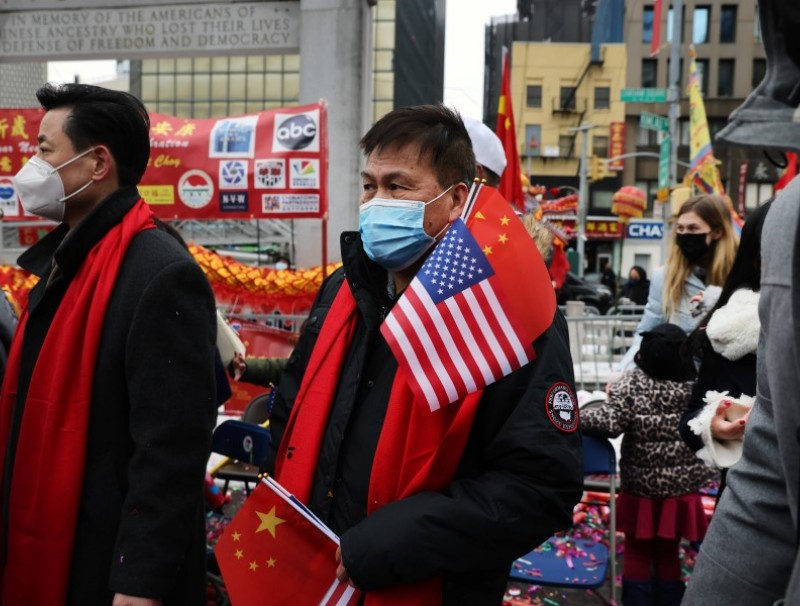 A man holds the US and China flags in a Lunar New Year ceremony in Chinatown on 12 February 2021 in New York City. (Spencer Platt/AFP)