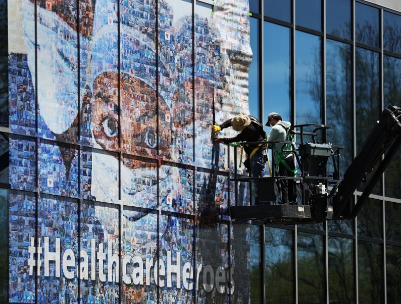 Workers put up a mural on a Northwell Healthcare building featuring healthcare workers who are on the frontlines during the Covid-19 pandemic on 5 May 2020 in New Hyde Park, New York. (Al Bello/Getty Images/AFP)
