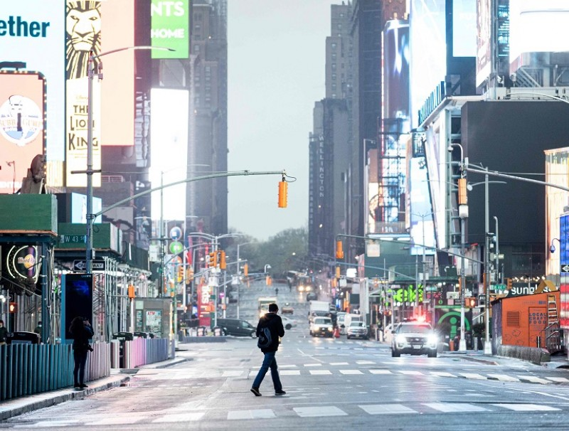 A man crosses the street at Times Square amid the Covid-19 pandemic on 30 April 2020 in New York City. (Johannes Eisele/AFP)