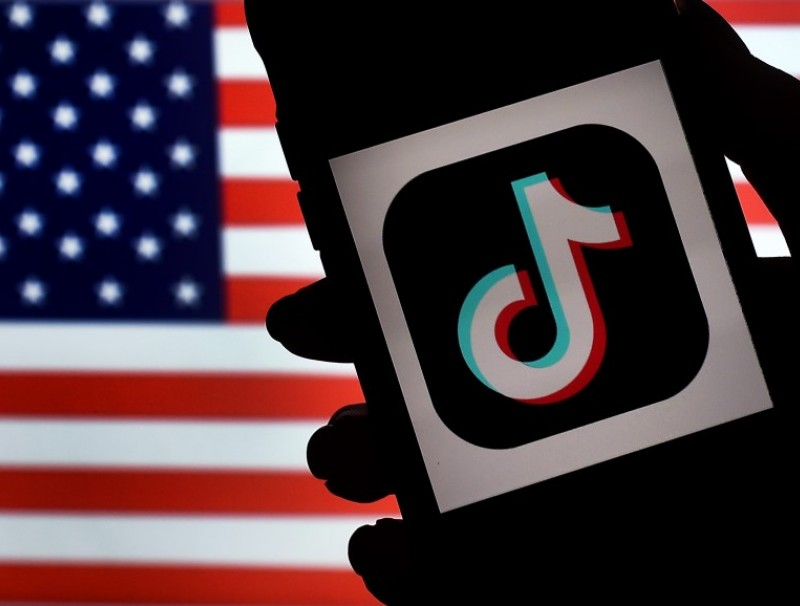 In this photo illustration, the social media application logo, TikTok is displayed on the screen of an iPhone on an American flag background on 3 August 2020 in Arlington, Virginia. (Olivier Douliery/AFP)