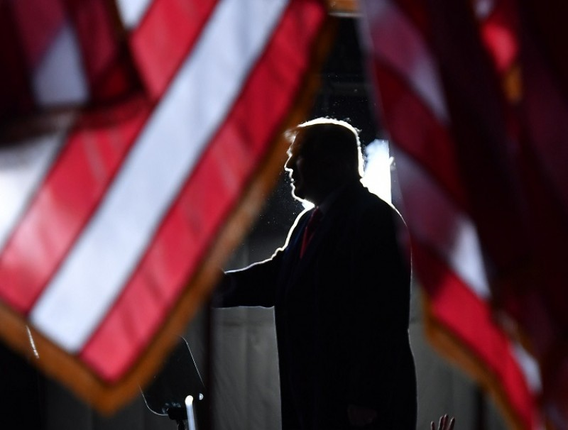"US President Donald Trump is seen behind US flags as he speaks to supporters at a ""Great American Comeback"" event at Central Wisconsin Airport in Mosinee, Wisconsin, on 17 September 2020. (Mandel Ngan/AFP)"