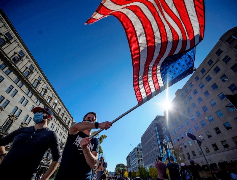 A man waves a US flag as people celebrate on Black Lives Matter plaza across from the White House in Washington, DC on 7 November 2020, after Joe Biden was declared the winner of the 2020 presidential election. (Eric Baradat/AFP)