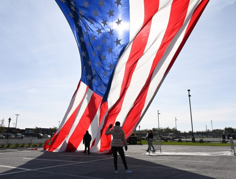 A US flag being hoisted on cranes outside the Chase Center in Wilmington, Delaware on 3 November 2020. (Roberto Schmidt/AFP)