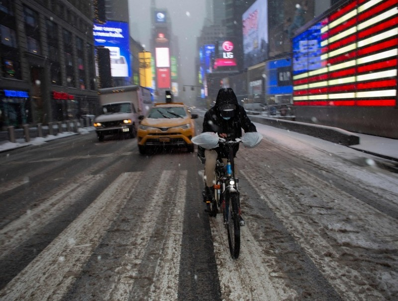 A man rides a bicycle as snow falls in New York's Times Square on 18 February 2021.(Kena Betancur/AFP)