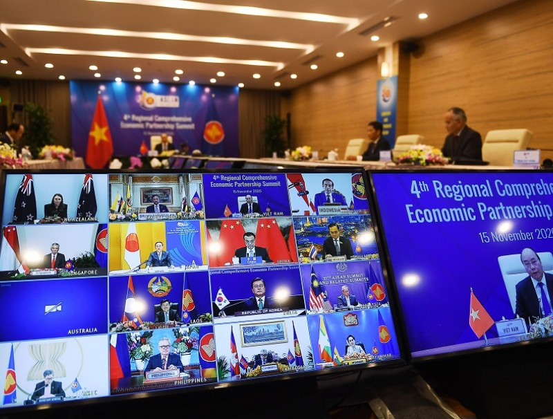 Vietnam's Prime Minister Nguyen Xuan Phuc is pictured on the screen (right) as he addresses his counterparts during the 4th Regional Comprehensive Economic Partnership (RCEP) Summit at the Association of Southeast Asian Nations (ASEAN) summit being held online in Hanoi on 15 November 2020. (Nhac Nguyen/AFP)