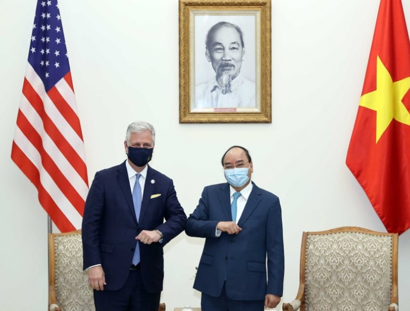 This picture taken and released on 21 November 2020 by the Vietnam News Agency shows Vietnam's Prime Minister Nguyen Xuan Phuc (R) bumping elbows to greet US National Security Advisor Robert O'Brien during a meeting in Hanoi. (Vietnam News Agency/AFP)